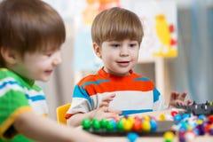 Spiel mit zwei Kinderbrüdern zusammen bei Tisch Lizenzfreie Stockbilder