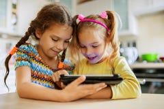 Spiel mit zwei kleinen Schwestern auf einem Tablet-PC Stockbilder