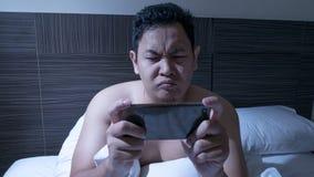 Spiel süchtig, männliches spielendes Spiel am intelligenten Telefon auf Bett um Mitternacht stockfotografie