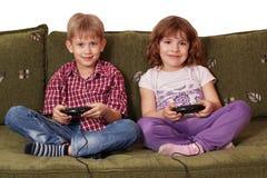 Spiel-Videospiel des Jungen und des kleinen Mädchens Stockfotos