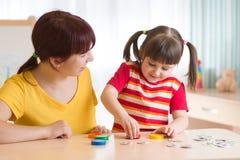 Spiele der jungen Frau mit Kinderlernspiel Stockbild