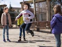 Spiele der Kinder Junge springt über das Seil Lizenzfreie Stockbilder