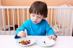 Spiele des kleinen Jungen mit Scheren und Perlen Stockbild