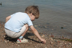 Spiele des kleinen Jungen mit Steinen Stockfotografie