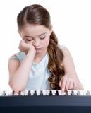 Spiele des kleinen Mädchens auf dem E-Piano. Stockbild