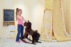 Spiele des kleinen Mädchens mit Schaukelpferd Stockbild
