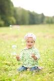 Spiele des recht kleinen Mädchens mit Seifenblasen draußen Lizenzfreies Stockbild