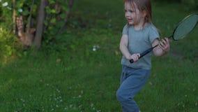 Spiele eines kleinen Mädchens im baminton stock video