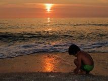 Spielen auf dem Strand am Sonnenuntergang Stockfotografie