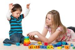 Spielen auf dem Teppich mit Blöcken Lizenzfreie Stockbilder
