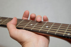 Spielen der Akustikgitarre: Flageolettmethode Stockbilder