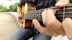 Spielen der Akustikgitarre im Park stock video footage