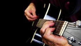 Spielen der Akustikgitarre Spielen Sie die Gitarre Lizenzfreie Stockbilder