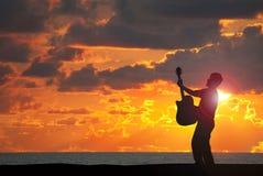 Spielen der Gitarre auf dem Strand am Sonnenuntergang Stockfotos