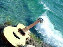 Spielen der Gitarre, die das Meer schaut Stockbild