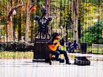 Spielen der Gitarre in einem Garten Stockfoto