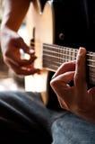 Spielen der Gitarre G-Spannweite stockbild