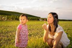 Spielen der Mutter und des Babys im Freien mit Seifenblasen Stockbilder