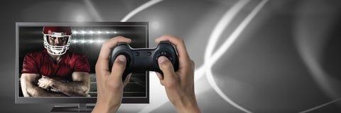 Spielen des Computerspiels des amerikanischen Fußballs mit Prüfer in den Händen Lizenzfreie Stockfotos