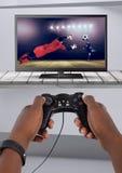 Spielen des Fußballcomputerspiels mit Prüfer in den Händen Lizenzfreie Stockbilder