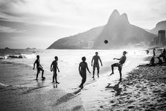 Spielen des Fußballs auf dem Strand Lizenzfreie Stockbilder