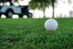 Spielen des Golfs und des Golfmobils Golfball ist auf dem T-Stück für ein Golf Lizenzfreies Stockfoto