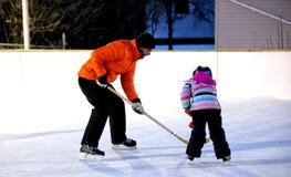 Spielen des Hockeys auf Eisbahn im Freien im Winter stockbild