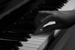 Spielen des Klaviers im Studio mit Schwarzweiss-Ton lizenzfreie stockbilder