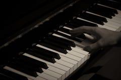Spielen des Klaviers im Studio mit Schwarzweiss-Ton stockbild