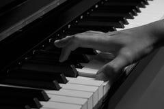 Spielen des Klaviers im Studio mit Schwarzweiss-Ton stockbilder