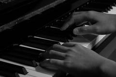 Spielen des Klaviers im Studio mit Schwarzweiss-Ton lizenzfreie stockfotografie