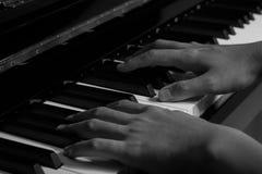 Spielen des Klaviers im Studio mit Schwarzweiss-Ton lizenzfreie stockfotos