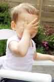 Spielen des kleinen Mädchens schüchtern Lizenzfreie Stockfotos