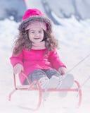 Spielen des kleinen netten süßen Mädchens im Freien im Winterschneepark lizenzfreie stockbilder