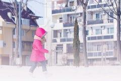 Spielen des kleinen netten süßen Mädchens im Freien im Winterschneepark stockfotografie