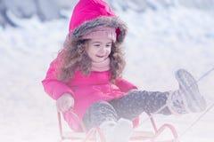 Spielen des kleinen netten süßen Mädchens im Freien im Winterschneepark lizenzfreies stockbild