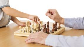 Spielen des Schachs, des Kindes und der älteren Hände, Kinderjungen-bewegliches Pfand Lizenzfreie Stockbilder