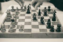 Spielen des Schachs, des Kindes und der älteren Hände, Kinderjunge bewegliches knigh Lizenzfreie Stockfotos