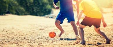 Spielen des Strandfußballs lizenzfreie stockbilder