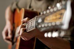 Spielen einer Akustikgitarre mit zwölf Zeichenketten Lizenzfreie Stockfotos