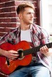Spielen seiner Lieblingsmelodie Hübscher junger Mann, der Akustikgitarre spielt und durch das Fenster schaut Stockfoto