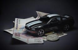 Spielen Sie Auto auf Geld, auf einem schwarzen Hintergrund Stockbild