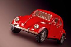 Spielen Sie Auto der roten Farbe gegen einen dunklen Hintergrund Stockfotografie