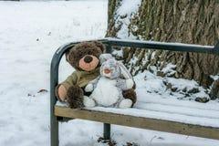 Spielen Sie Bären und einen Hasen, der auf der Bank im Winter sitzt Stockbild