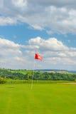 Spielen Sie bewölkten blauen Himmel der roten Fahne des grünen Grases des Feldes Golf lizenzfreies stockbild