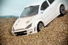 Spielen Sie das laufende Auto, das in eine Sanddüne und in Belege zerschmettert wird stockbild