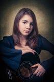 Spielen Sie das schöne jugendlich Mädchen der Gitarre…, das Musik mit einer Gitarre spielt Stockfotografie