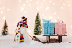 Spielen Sie den Schneemann, der kleinen hölzernen Pferdeschlitten mit Weihnachtsgeschenken zieht Stockfotografie