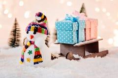 Spielen Sie den Schneemann, der kleinen hölzernen Pferdeschlitten mit Weihnachtsgeschenken zieht Lizenzfreie Stockfotografie