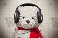 Spielen Sie den Teddybären mit einem roten Schal hörend Musik auf Kopfhörern Stockbild